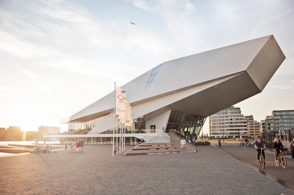 Biela moderna budova filmového instutu v Amsterdame pri zapade slnka