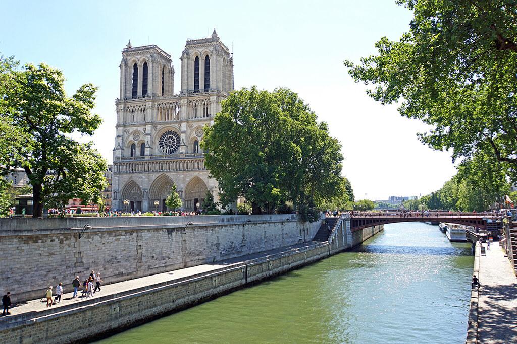 Vyhľad na priečelie krásne zdobenej bielej gotickej katedrály čiastočne zakrytej stromom ponad vodný kanál rieky seiny.