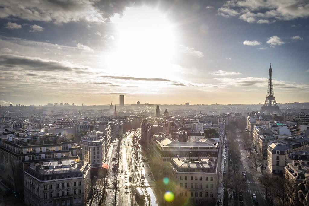 Výhľad na ulice historického centra Paríža zaliatých slnkom s modernou štvrťou a Eifelovou vežou v pozadí.