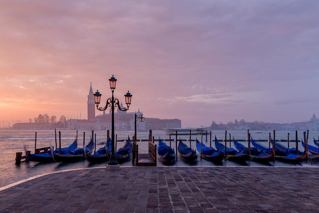 Západ slnka nad benátskymi gondolami v pozadí s bazilikou San Gorgio Maggiore