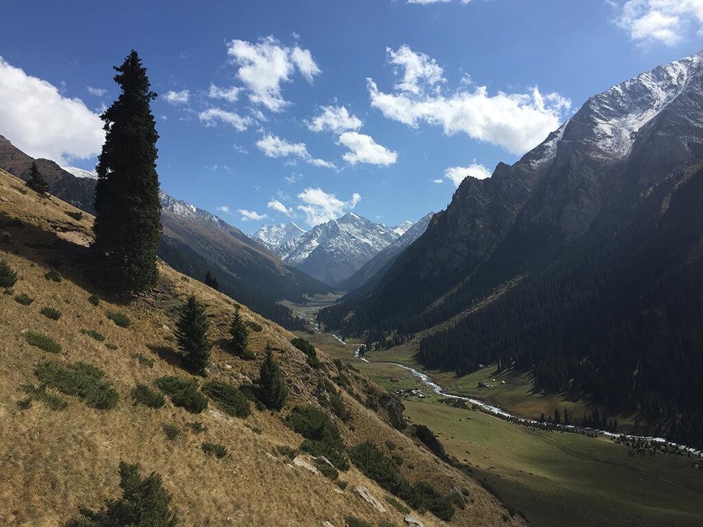 Výhľad na údolie ktorým preteká rieka v pozadíí so zasneženými kopcami