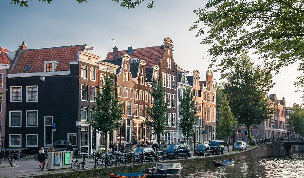 Vodny kanal s lodkami ktory lemuju stromy a domy s klasickou holandskou architekturou