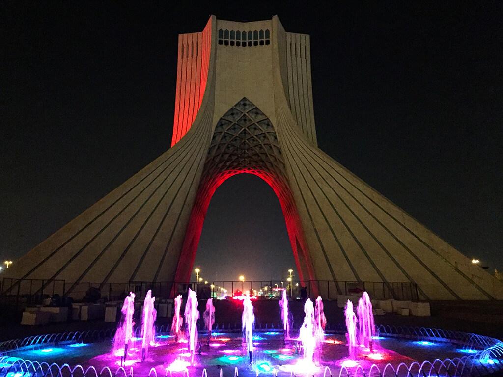 Nočný pohľad na oblúkovú vežu Azadi tower s vysvietenou fontánou v popredí