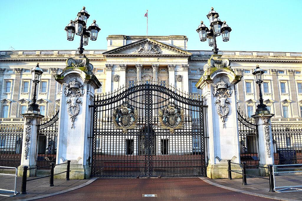 Nádherne zdobená brána Buckinghemského palácu v Londýne s lampami a palácom v pozadí.