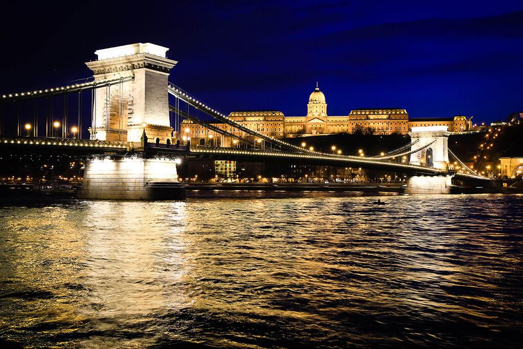 Krásne vysvietený reťazový most ponad rieku Dunaj s majestátnym hradom Budín na kopci v pozadí