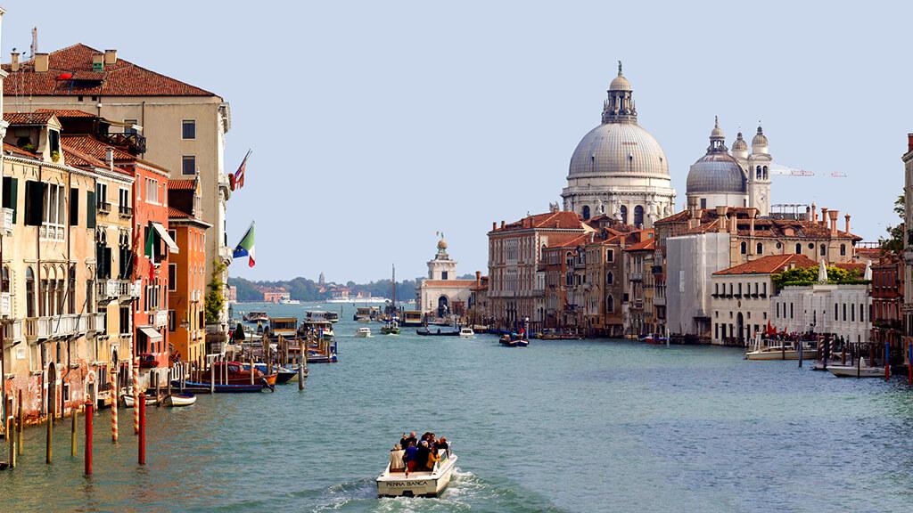 Najväčši vodný kanál rozdelujúci benátky na dve polovice s lodkami a nádhernou bazilikou Santa Maria della Salute v pozadí.