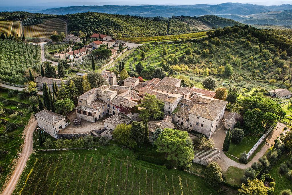 Letecký pohľad na vinárstvo uprostred klasickej toskánskej scenérie s viničom a zelenými stromami