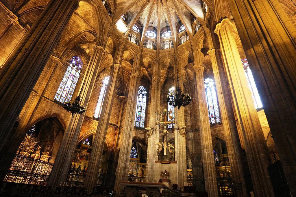 Bohato zdobený interíer barcelonskej katedrály s vysokymi stĺpmi, klenbou a oltárom. Záber z interiéru.