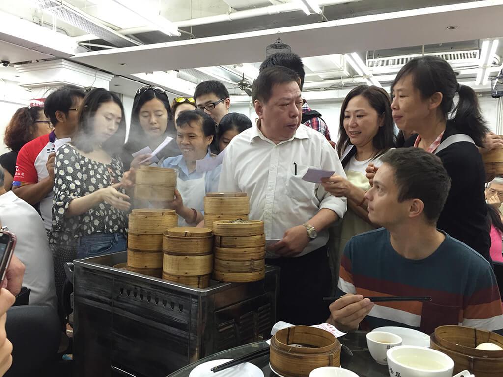 Ľudia tlačiaci sa pri stolíku s jedlom ukrytom v okrúhlych drevených nádobkach.