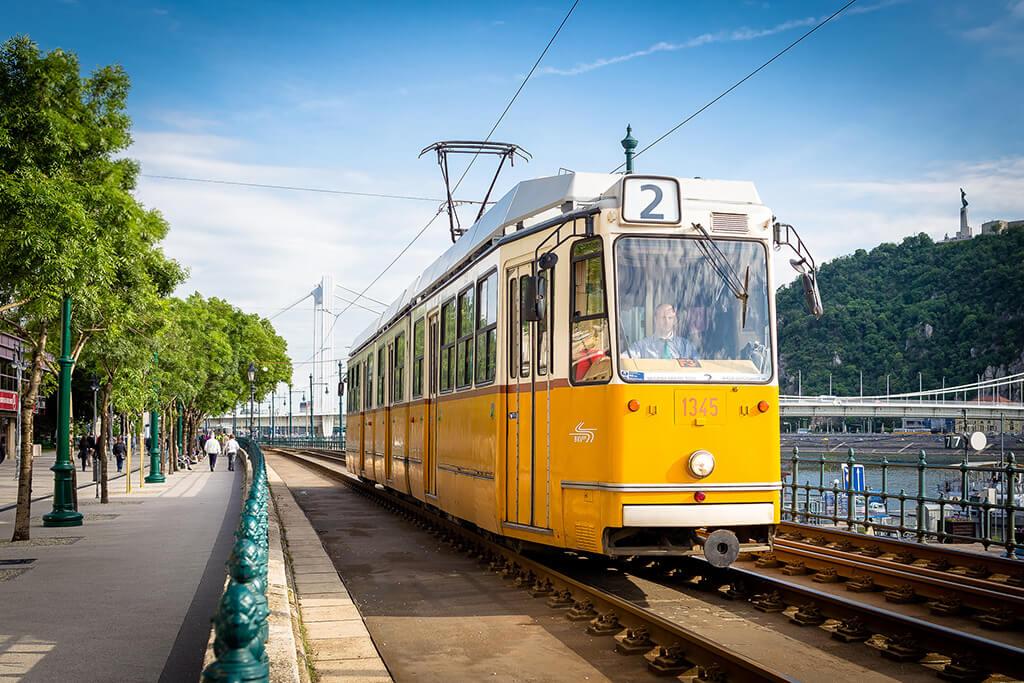 Stará klasická žltá električka číslo 2 na promenáde pri Dunaji s mostom a modrou oblohou v pozadí
