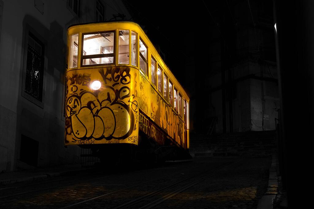 Svietiaca žltá nočná električka pomaľovaná grafitmi