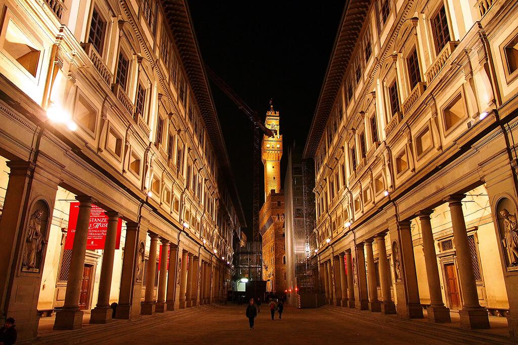 Osvetlená nočná galéria s výhlľadom na Arnolfovu vežu Palazzo Viecchio.