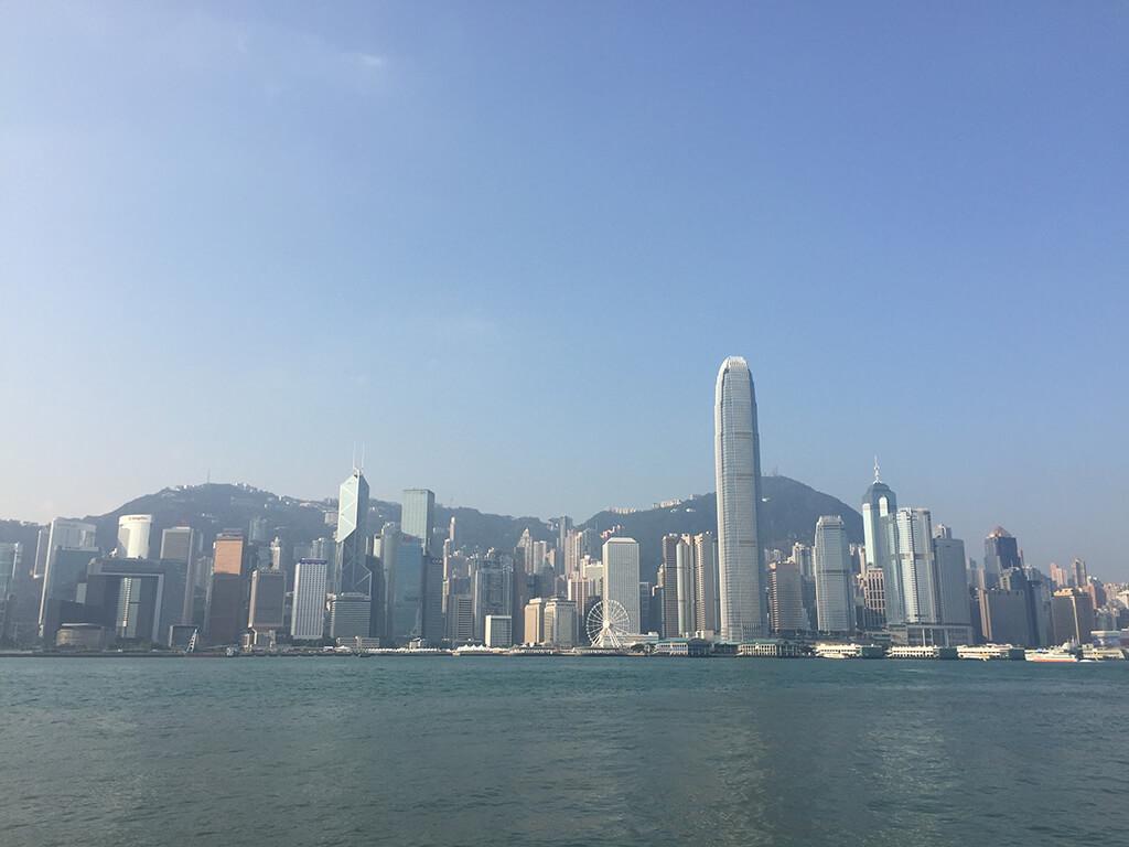 Pohľad na výškové budovy na HongKong Island s Victoria Peak v pozadí z pevninskej časti Hong Kongu.