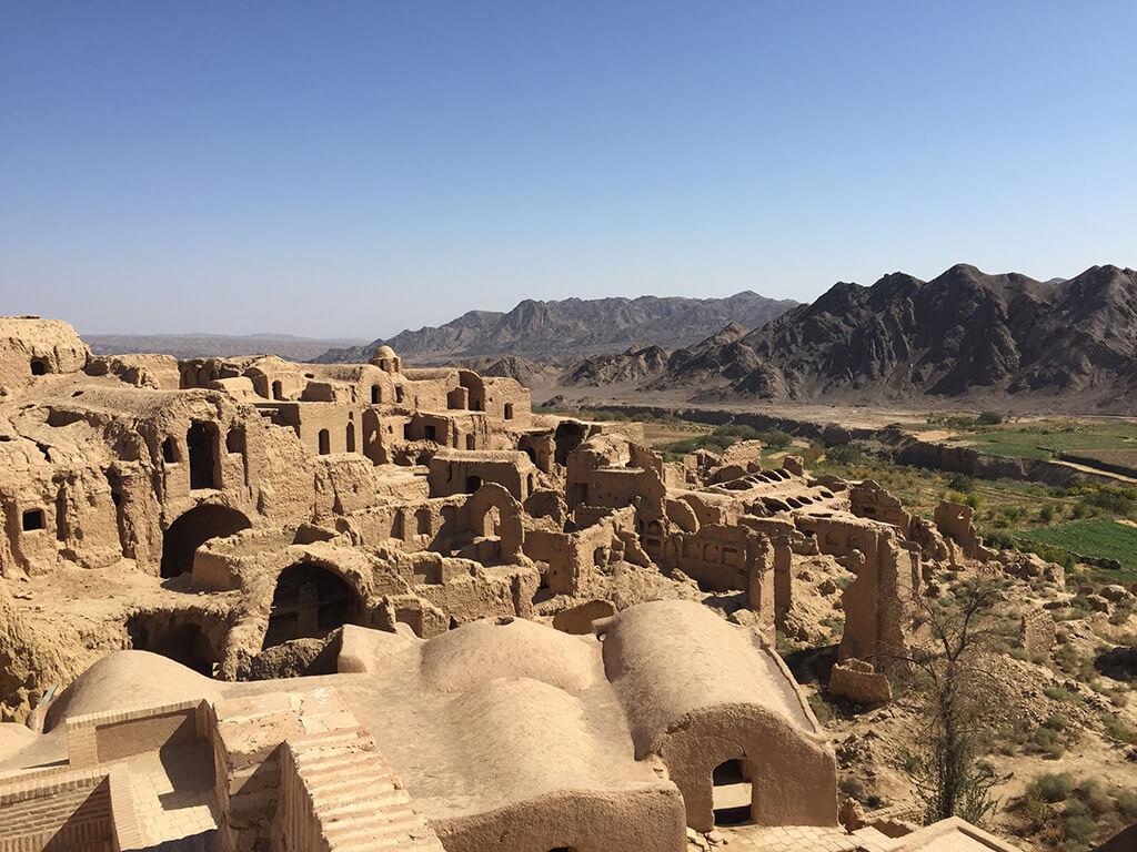 Rozpadajúce sa starodávne hlinené mesto so zeleným údolím a kopcami v pozadí