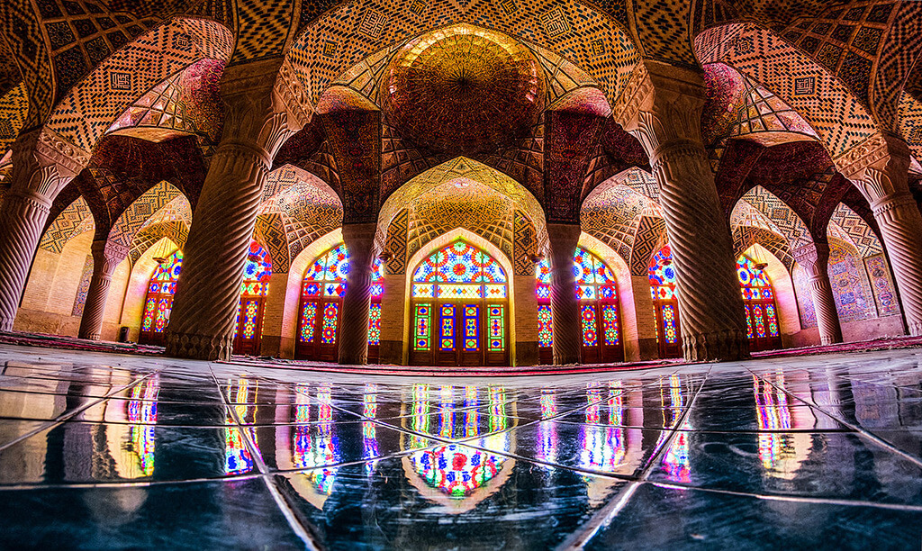 Pohľad z vnútra mešíty pomedzi stĺpové klenby na nádherne sfarbené vytrážové okná ktoré sa odrážajú na lesklej podlahe