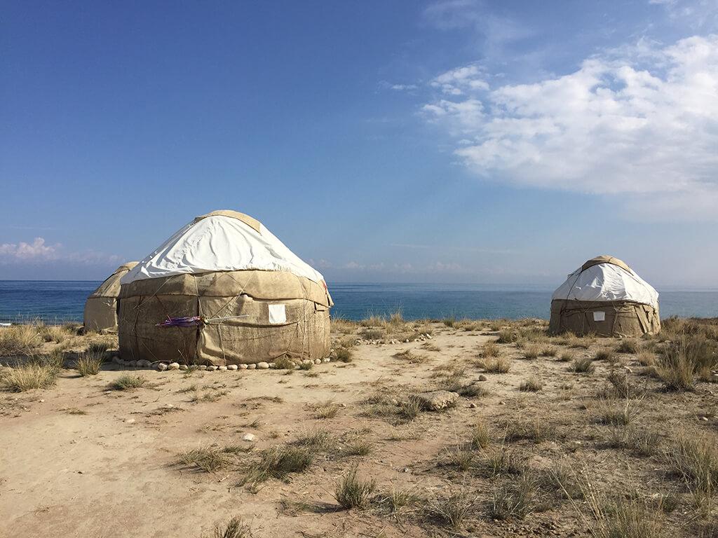 Pohľad na tradičné jurty na ktoré dopadajú slnečné lúče v pozadi s jazerom Yssyk Kul