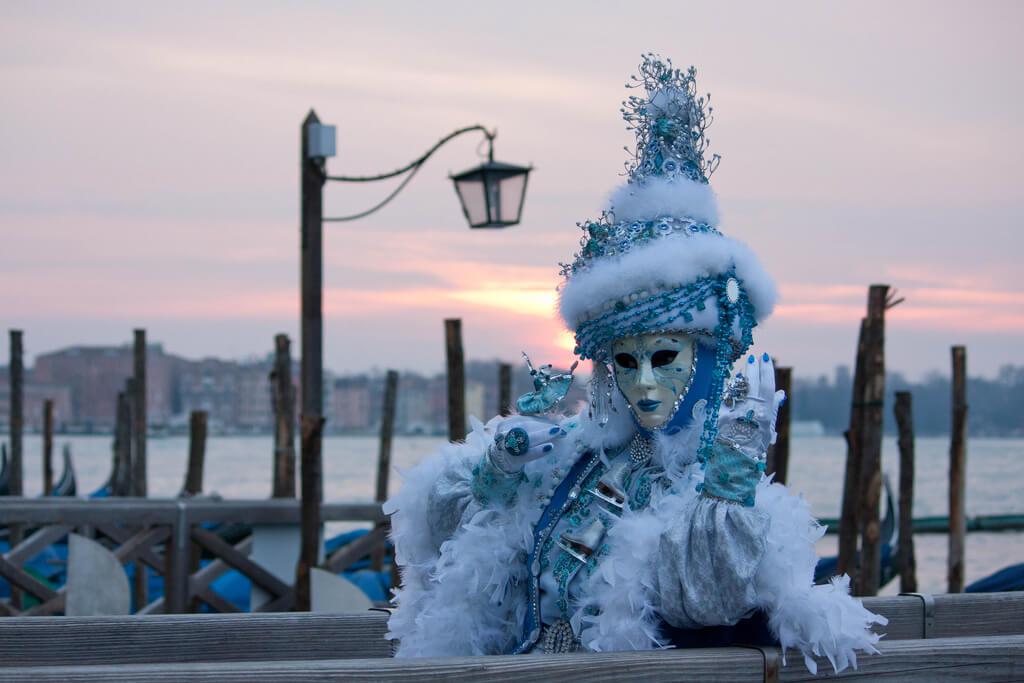 Nádherne zdobené bielo modré oblečnie postavy počas benátskeho karnevalu s gondolami a lamponom na pozadí