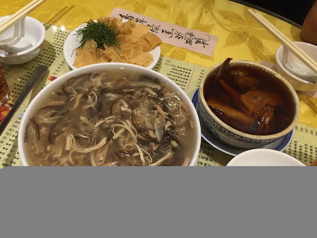 Hadia a korytnačia polievka na stole so žltým obrusom vo väačšej a menšej myske.