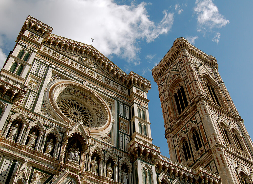 Bohato zdobene priečelie gotického kostola s vežou po pravej strane.