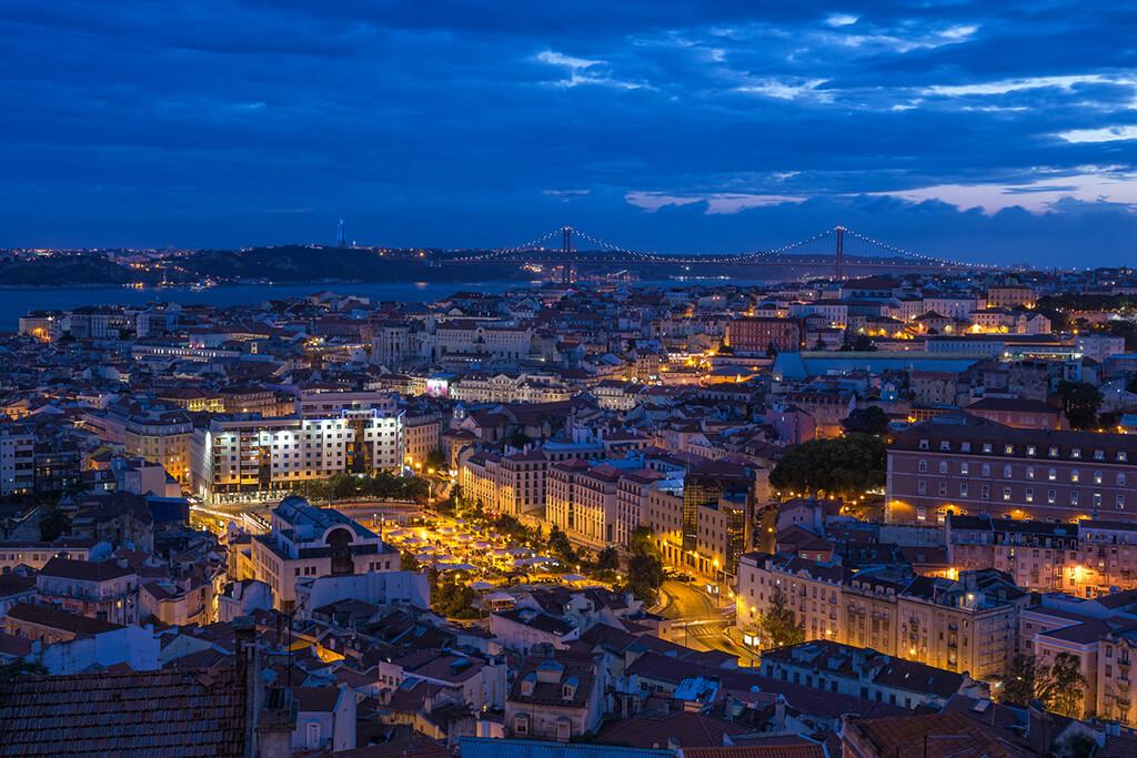 Nočný pohľad na Lisabon s množstvom svetiel a s mostom v pozadí.