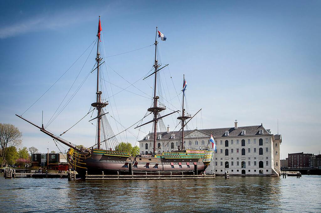Biela budova námorného múzea v amsterdame s replikou trojstaznovej lode v popredi