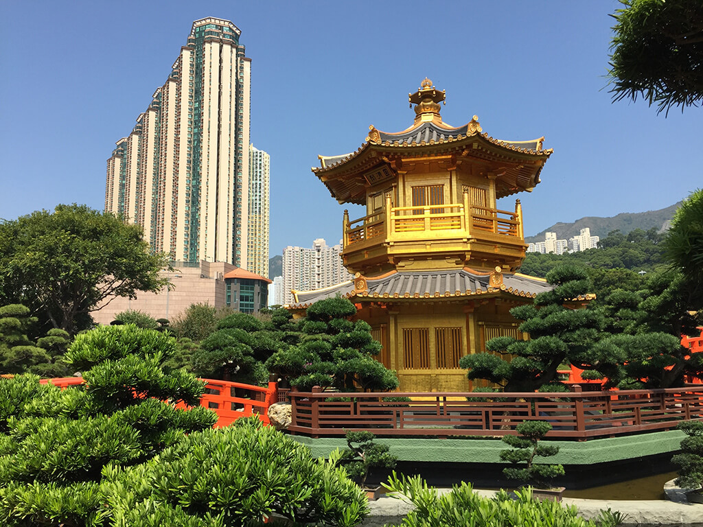 Čínsky chrám obkolesený zeleňou záhrade uprostred mesta s betónovým vežiakom v pozadí