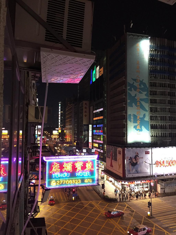 Nočný pohľad z okna budovy na rušnú ulicu nathan road s množstvom svetelných rekám.