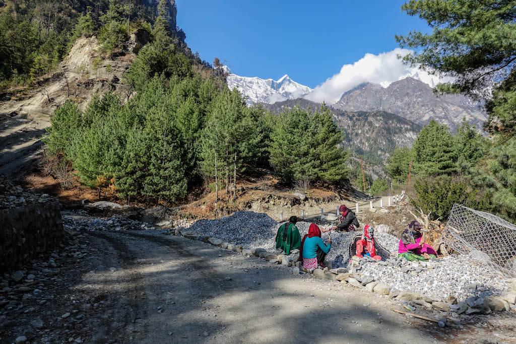 Pohľad na cestu na okraji lesa a pracujúcich ľudí v diaľke so zasneženým vrcholom Annapurny II zakrytý mrakmi