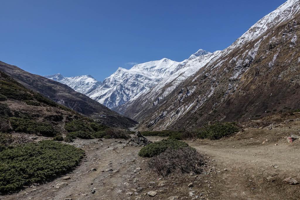 Spätný pohľad do údolia ktoré v diaľke uzatvárajú zasnežené končiare Annapurien a Gangapurny.