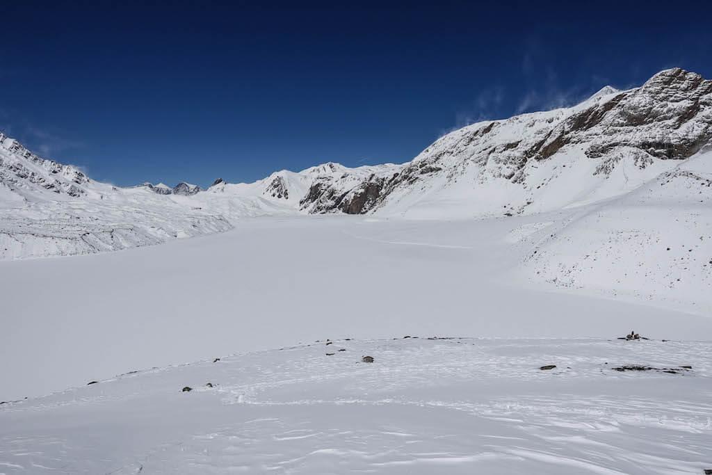 Pohľad na zamrznuté jazero pokryte snehom, ktoré vypadá ako dokonalé klziisko s čistou modrou oblohou v pozadí a bielymi štítmi po oboch stranách