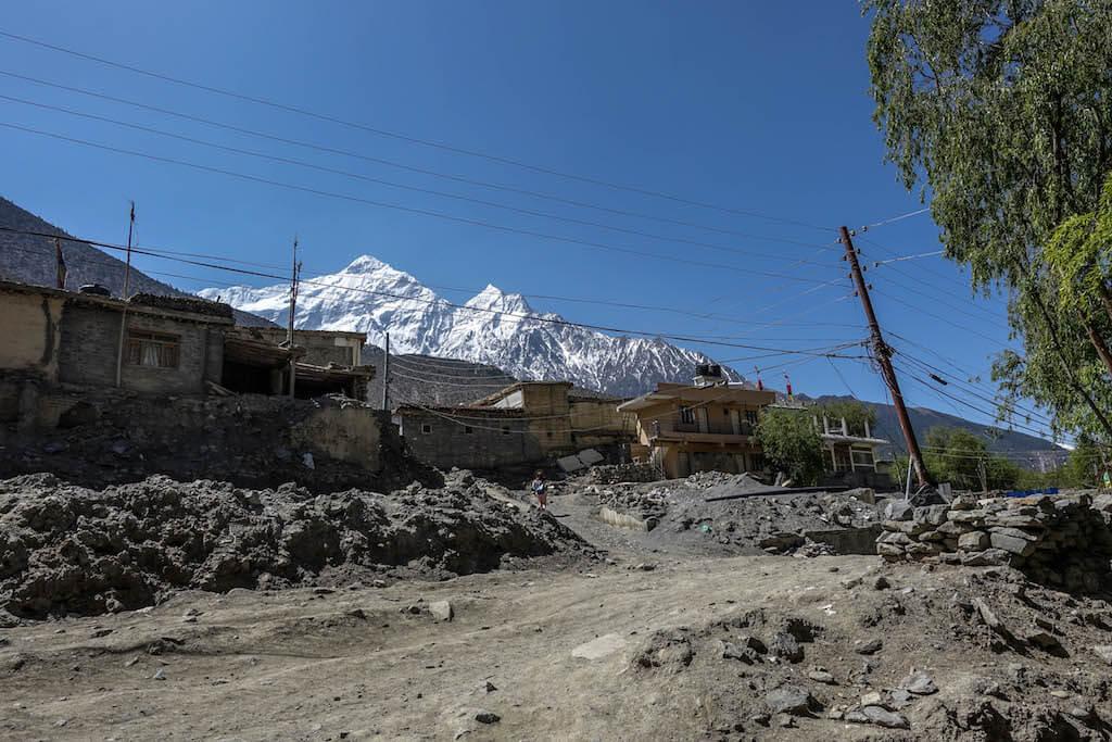 výhľad z prašnej ulice na domy nad ktorými sa týčia vysoké biele štíty Nilgiri