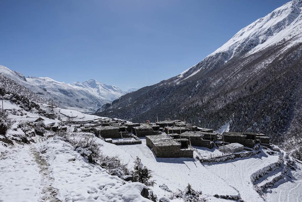 Zasnežená krajina s domčekmi s rovnými strechami v dedine Khangsar za ktorou sa dvíhajú mohutné hory