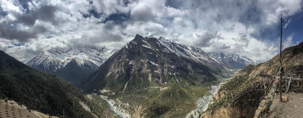 Pohľad z protilľahlej strany údolia na majestátne hory zahalené do bielych mrakov a na rieku ktorá sa pred nimi plazí ako had