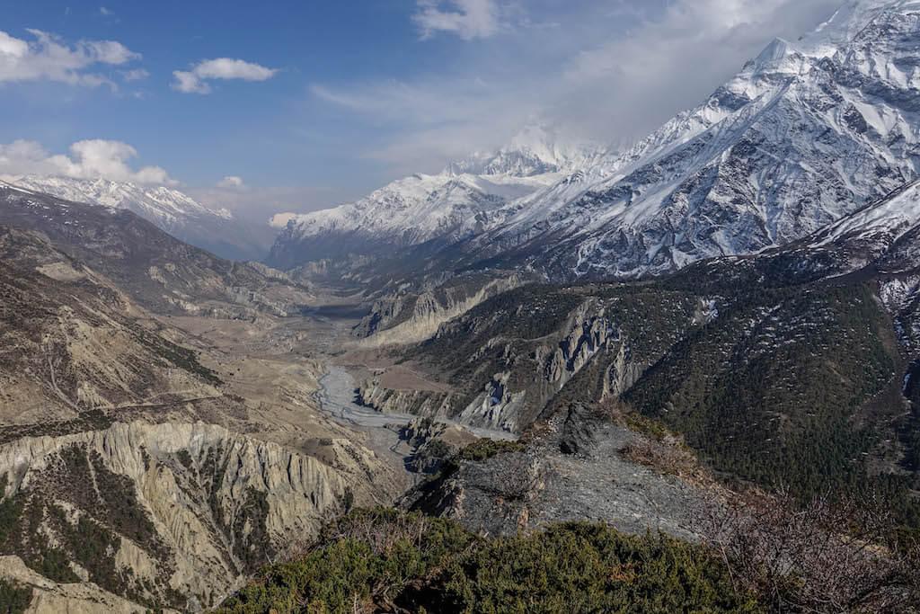 Výhľad do klukatiaceho sa údolia s riekou, ktoré postupne stúpa od vypráhlej krajiny cez zelené lesy až ku zasneženým štítom himalájskych