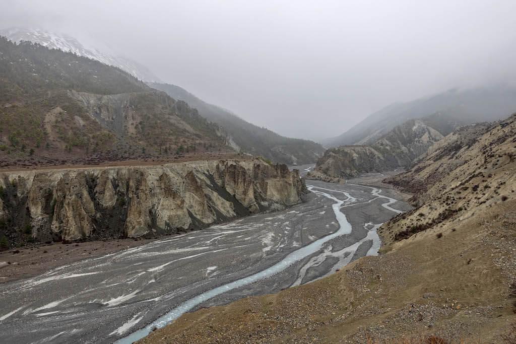 Koryto rieky v objati kopcov, ktoré sa strácajú v hustých mračnách