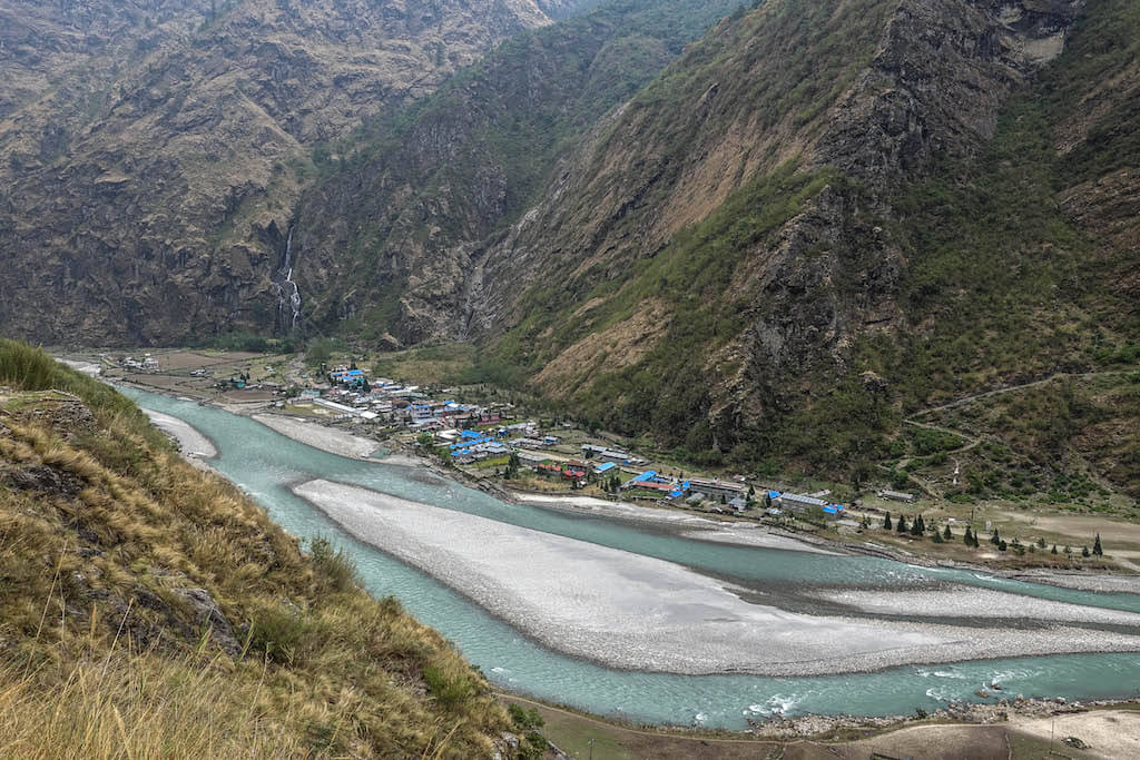 Malá dedinka v údolí pri rieke za ktorom sa dvíhajú mohutné skaly s vodopádmi