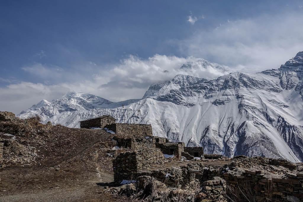 Domy opustenej nepálskej dediny v pozadi so zasneženými štitmí v pozadí