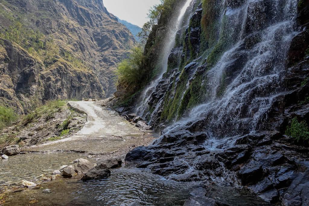 Vodopád stekajúci po kolmej zelenej stene priamo na cestu