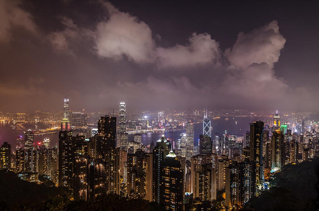 Pohľad v noci na tísíce vysvietených vežiakov ktoré sa rozprestierajú pod vami spolu s prístavom.