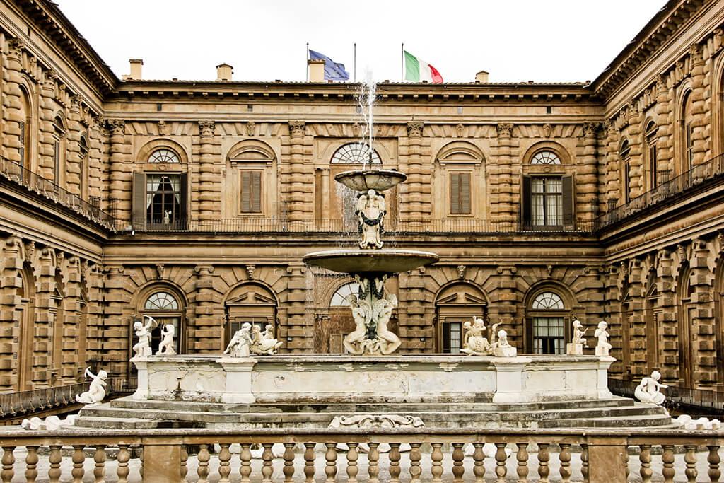 Veľká zdobená kruhová fontána s palácom v pozadí.