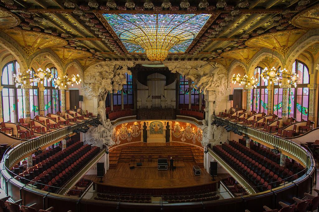 Nádherne zdobený interiér koncertnej sály s dvojposchodovým balonom, sedadlami a bohato zdobeným skleneným stropom