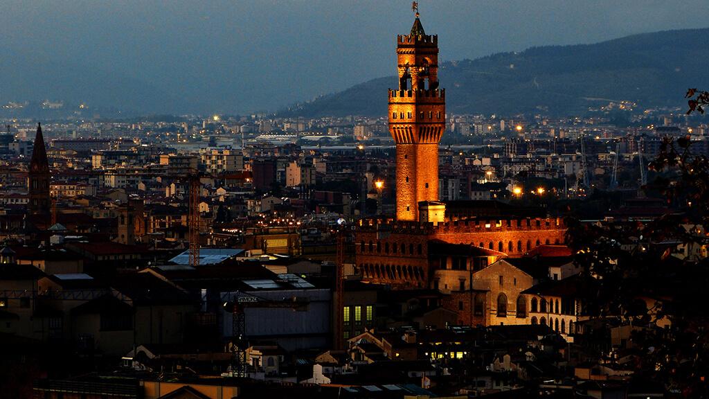 Do oranžova vysvietený Palazzo Viecchio počas noci s historickou Florenciou v pozadí.
