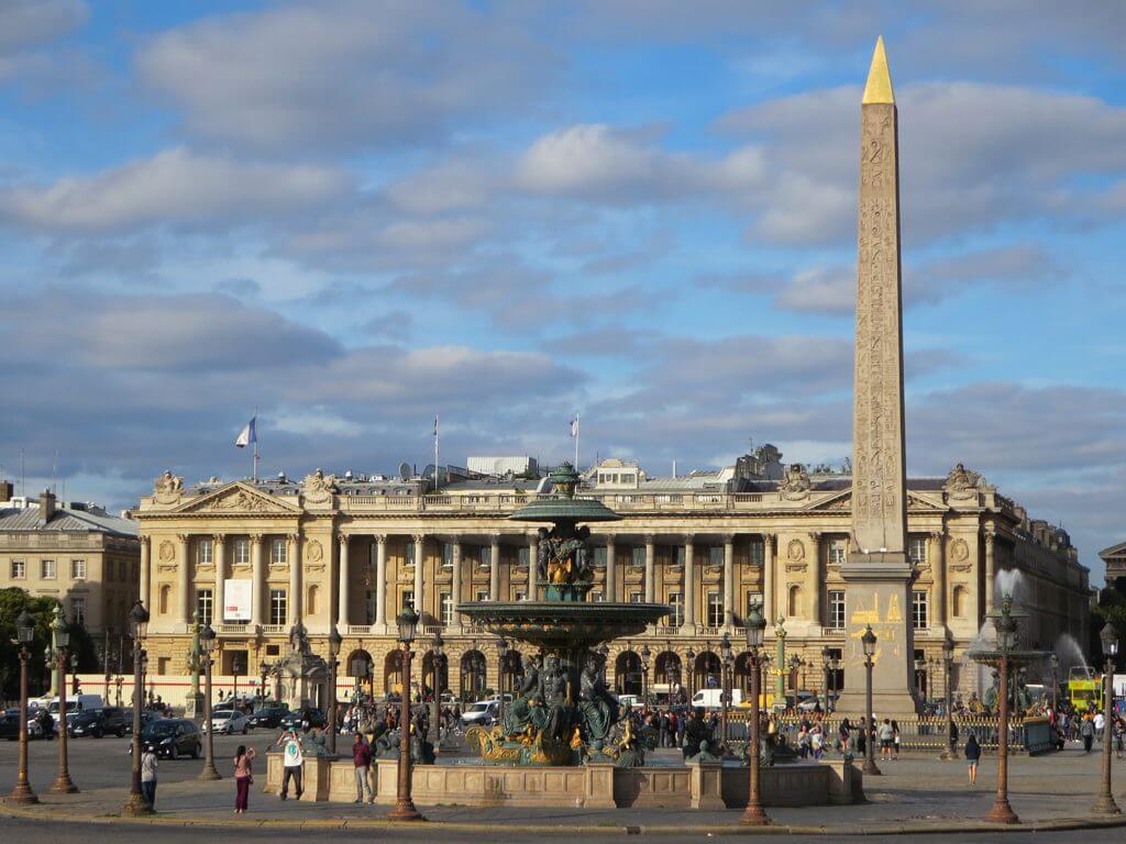 Egyptský obelisk pri fontáne na námestí plnom ľudí s palácom v pozadí