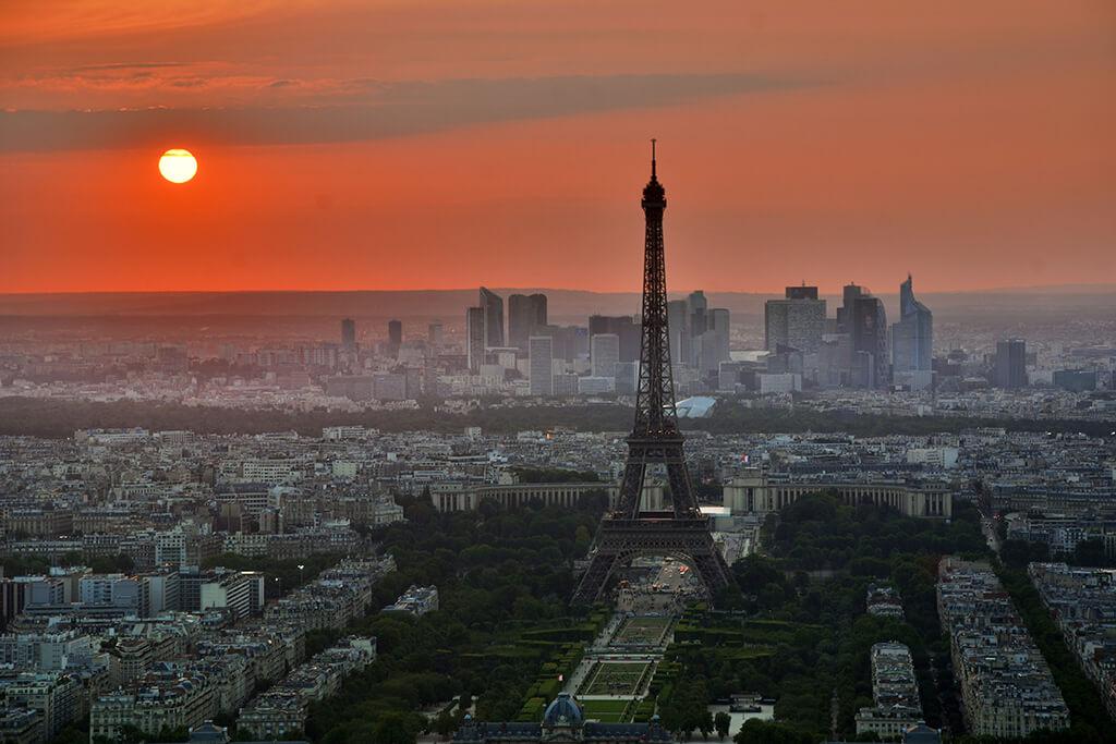 Oranžové zore nad Parížom pri západe slnka. Výhlľad na Eifelovu vežu s moderným centrom Paríža na pozadí.