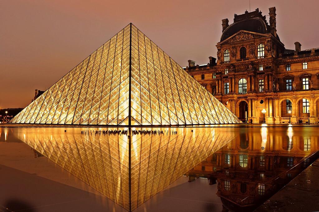 Pohľad na sklenenú pyramídu a historickú budovu paláca parížskeho múzea Louvre, ktoré sa odrážajú na hladine vody.