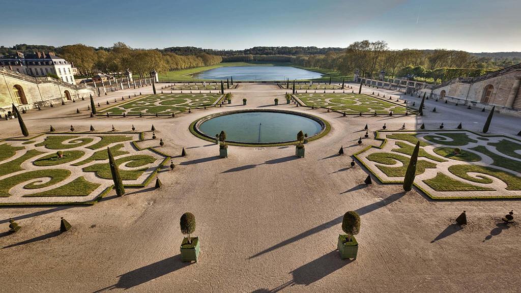 velka barokova zahrada s kruhovym jazierkom a velkym jazerom a stromami v pozadi