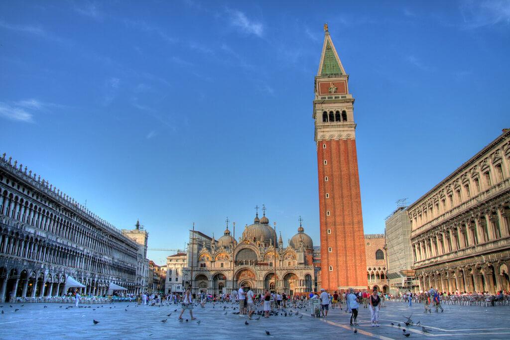 Vydláždené námestie svätého Marka v Benátkach plné ľudí s nádherne zdobenou bazilikou a vysokou vežou Kampanilou (zvonica)