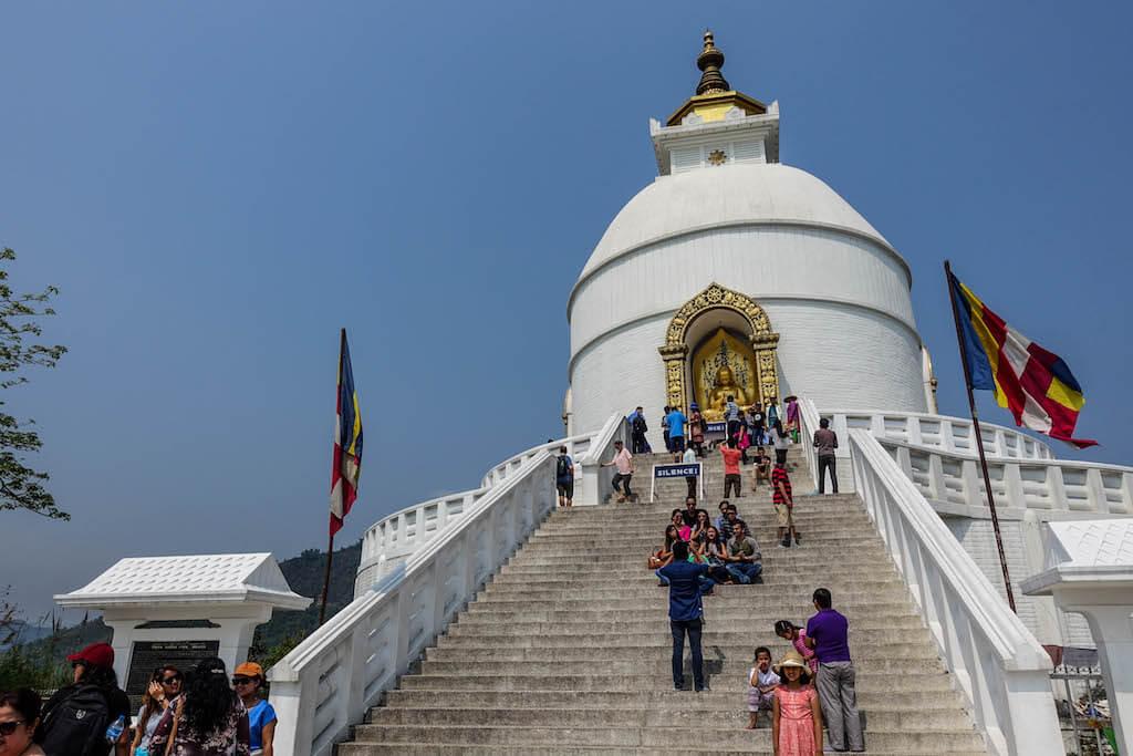 Biela pagoda so ztlatým budhom ku ktorému vedie množstvo širokých s chodou s ľudmi a modrou oblohou