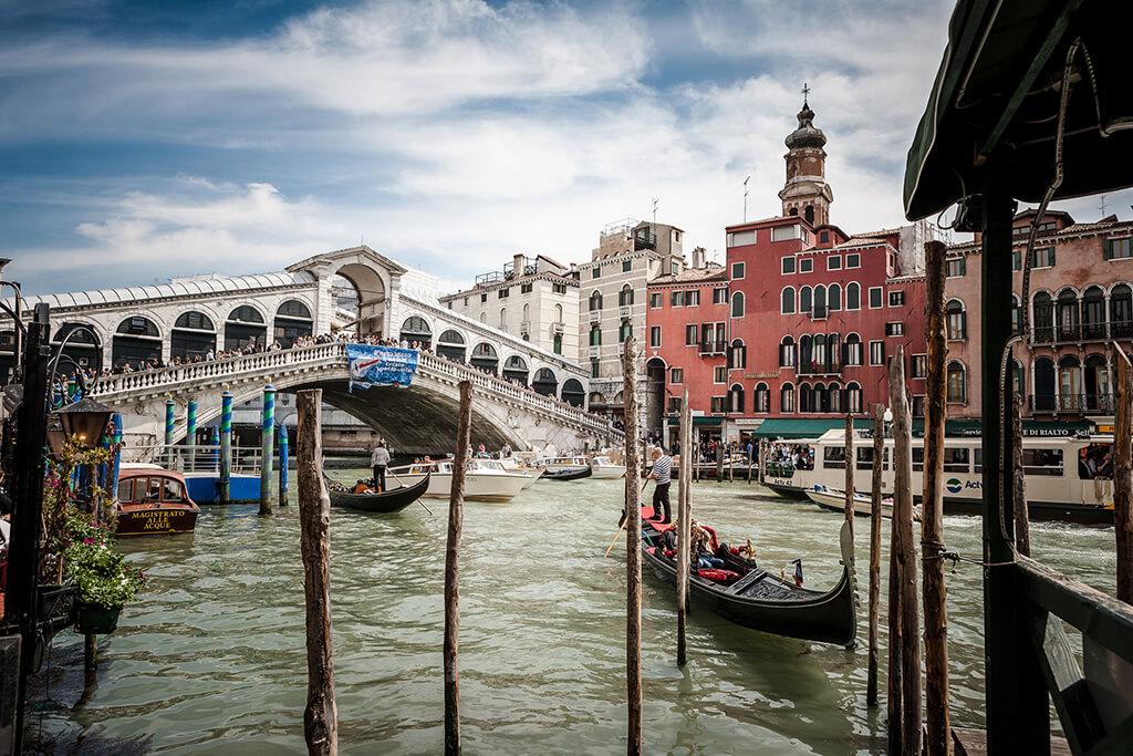 Veľký kanál v Benátkach s mostom Ponte di Rialto gondolami a okolitými budovami.