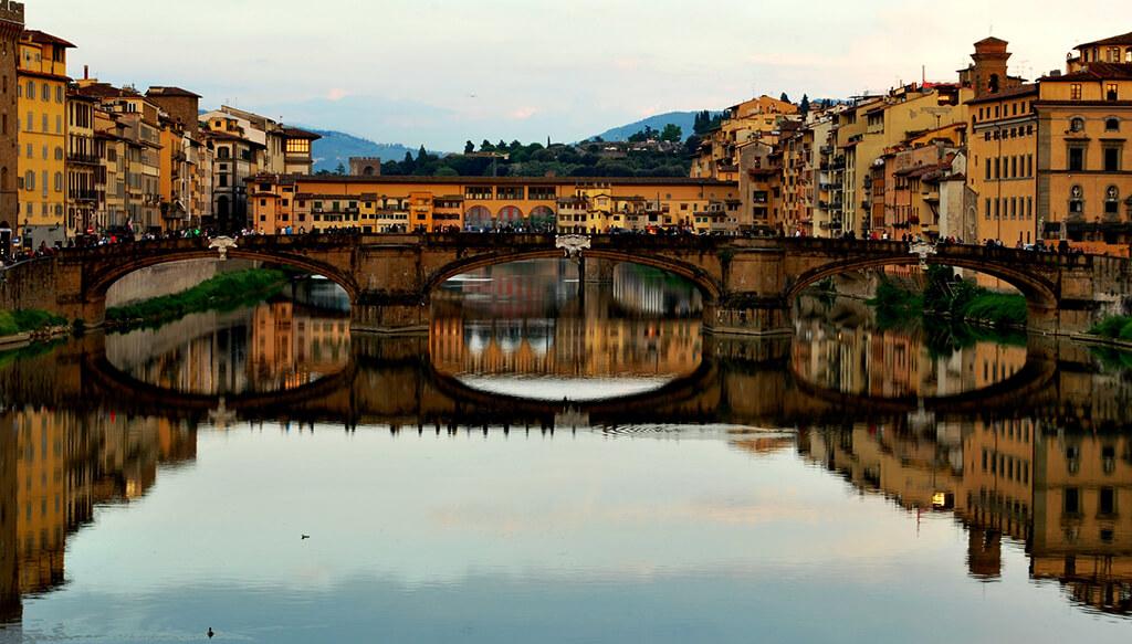 Pohľad z mosta ponad rieku Arno pri západe slnka na historické mosty Florencie s najznámejším Ponte Viecchio v pozadí.